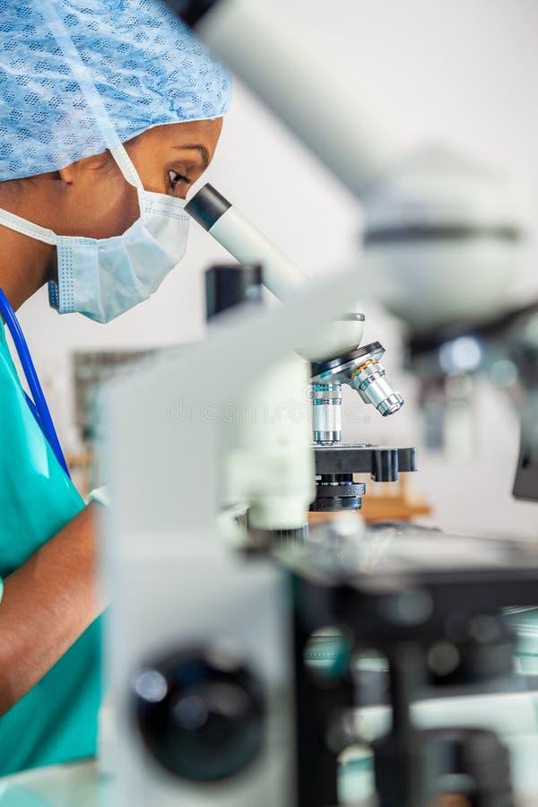 Азиатские доктор или ученый женщины используя микроскоп в лаборатории стоковые фото
