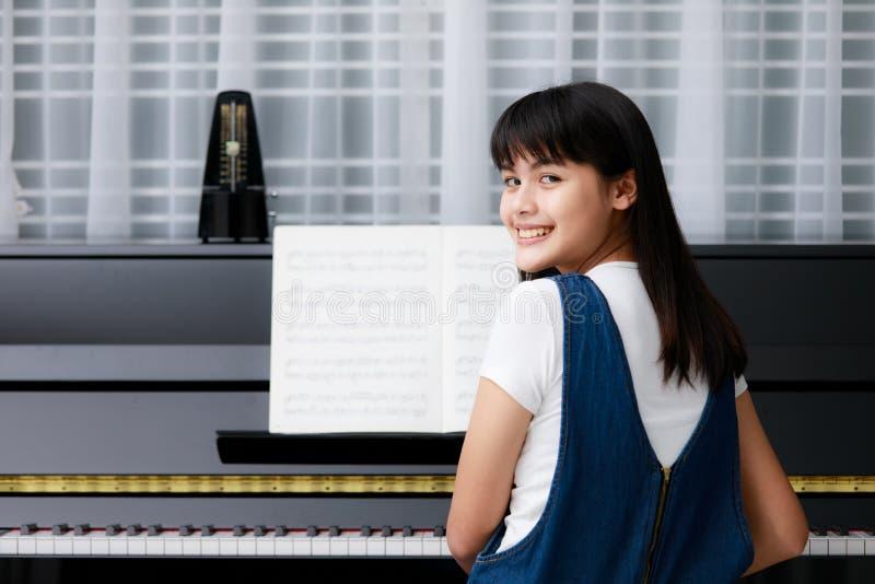 Азиатские девушка и рояль стоковая фотография