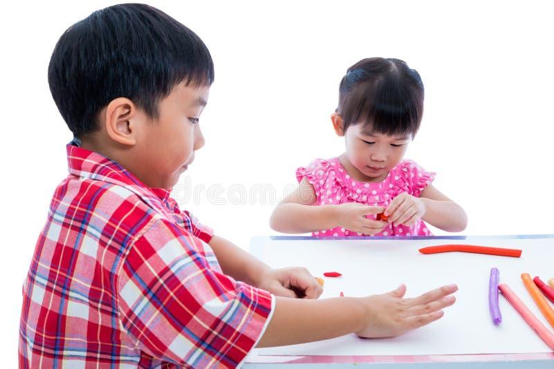 Азиатские дети играя с глиной игры на таблице Усильте imagi стоковые изображения rf