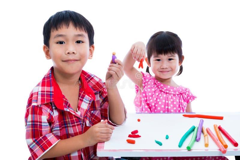 Азиатские дети играя с глиной игры на таблице Усильте imagi стоковое фото rf