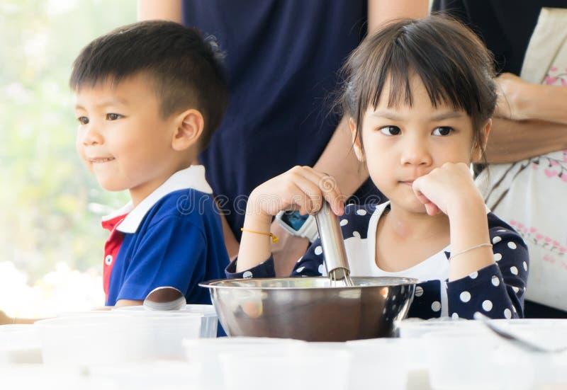 Азиатские дети наслаждаясь воспитательным уроком кулинарии стоковые изображения