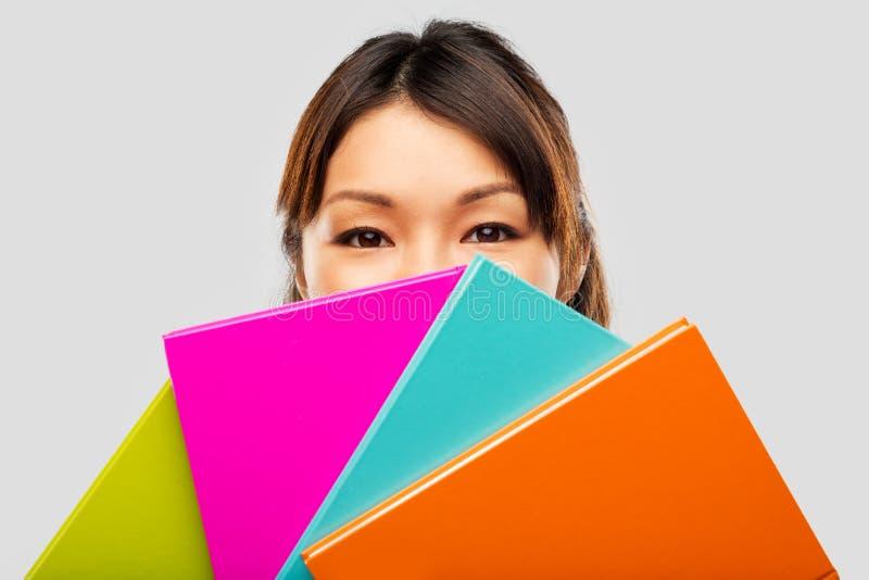 Азиатские женщина или студент пряча за тетрадями стоковое изображение rf