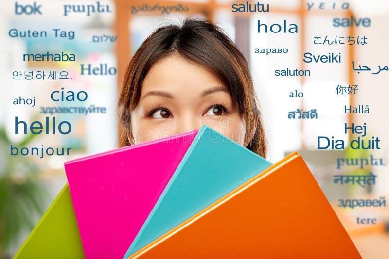 Азиатские женщина или студент пряча за тетрадями стоковая фотография