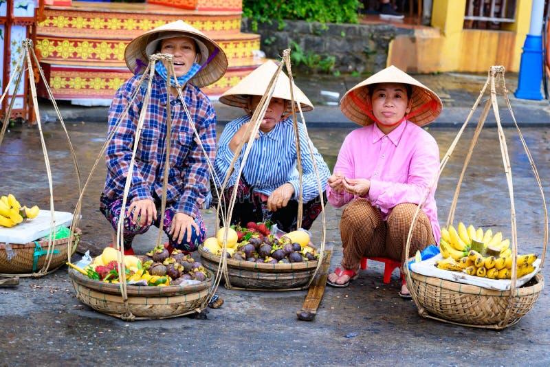 Азиатские женщины продавца плода с традиционными корзинами в туристском назначении Hoi, въетнамских женщинах в Hoi, Вьетнаме стоковая фотография