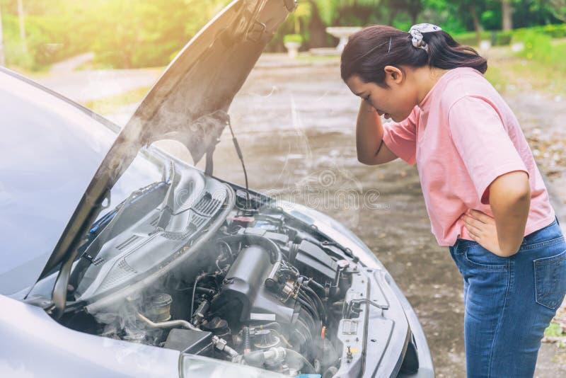 Азиатские женщины тревожатся и усиливаются тревогу с автомобилем стоковые фото