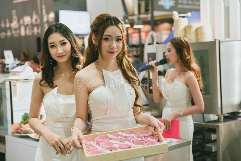 Азиатские женщины pritty дают образец блюда к клиенту в экспо индустрии продовольственного рынка на Бангкоке стоковое изображение