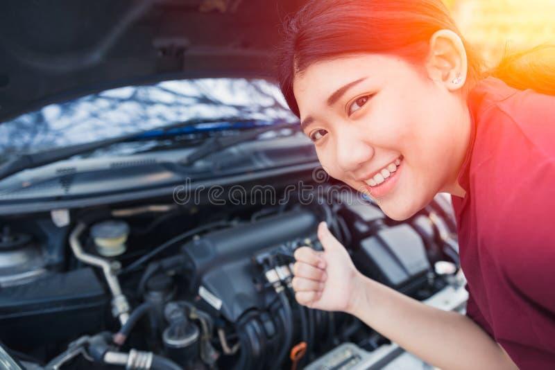 Азиатские женщины thumbs вверх по хорошей проверке двигателя автомобиля вверх стоковые изображения rf