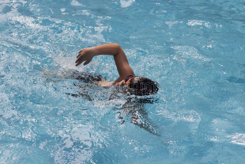 Азиатские заплывы переднего ползания мальчика в бассейне стоковые фото