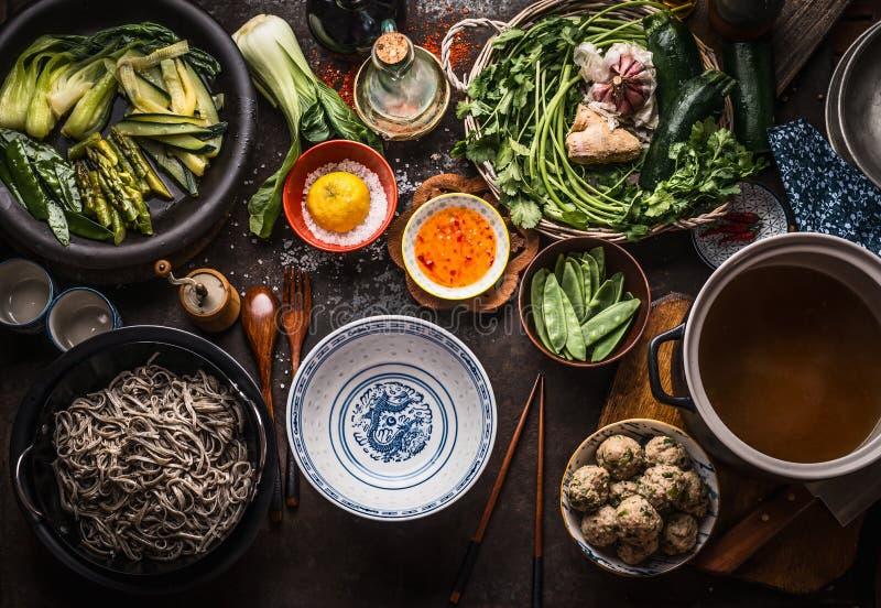 Азиатские ингредиенты супа лапши: различные свежие и сваренные зеленые овощи, травы и специи, шарики мяса, лапша soba и стоковые изображения