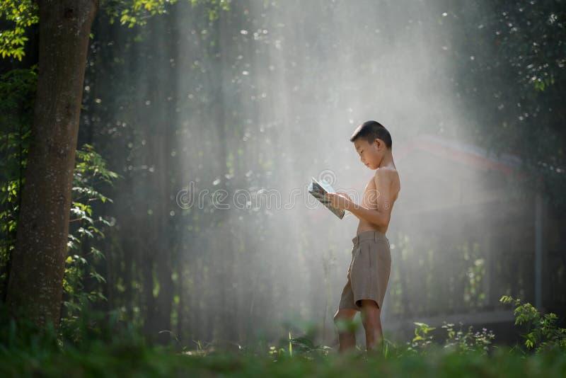 Азиатские книги чтения студентов в сельской местности Таиланда, сельском chil стоковое изображение