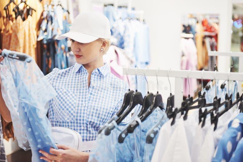 азиатские красивейшие кавказские одежды одевая женскую счастливую внутри помещения смотря женщину магазина модельной покупкы поку стоковое фото rf