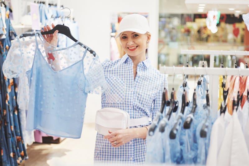 азиатские красивейшие кавказские одежды одевая женскую счастливую внутри помещения смотря женщину магазина модельной покупкы поку стоковая фотография
