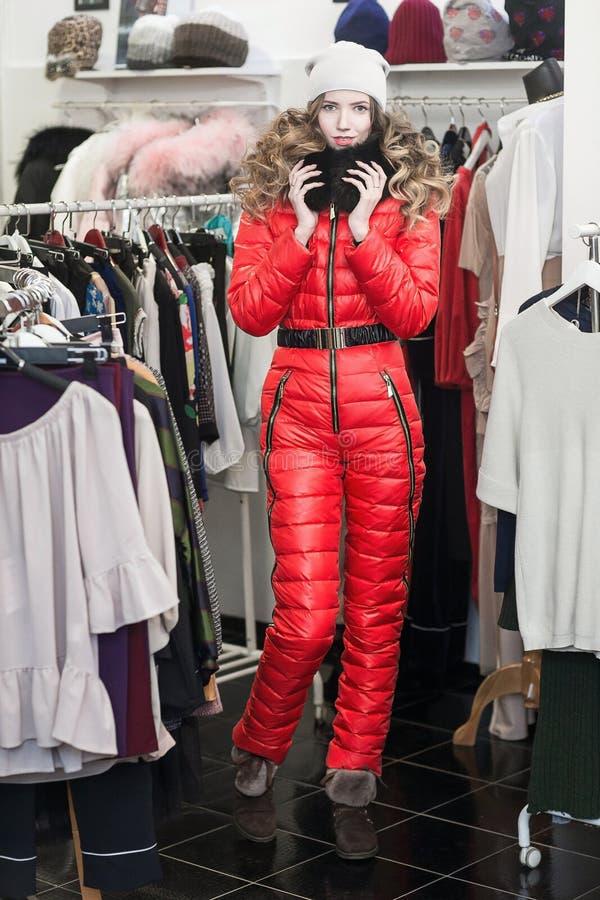 азиатские красивейшие кавказские одежды одевая женскую счастливую внутри помещения смотря женщину магазина модельной покупкы поку стоковое изображение