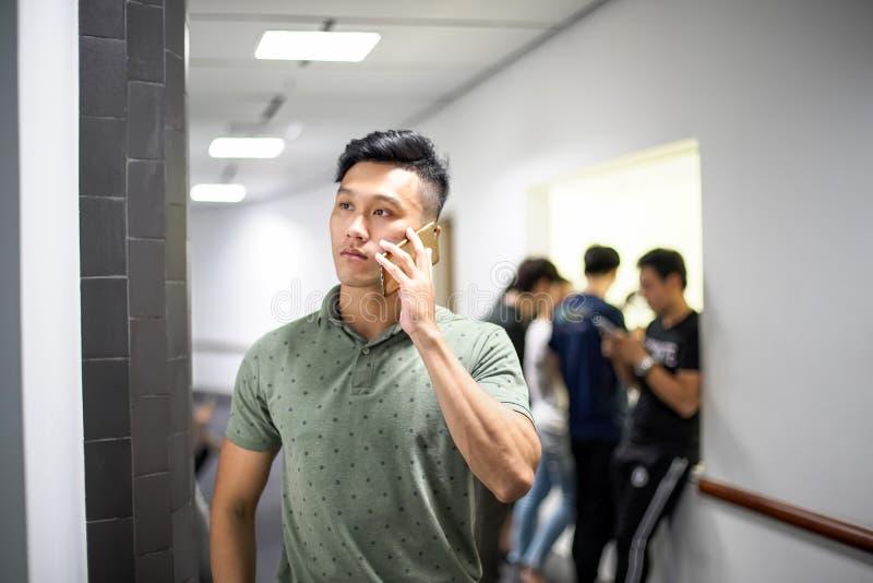 Азиатские красивые люди говоря счастливо по телефону | Улыбка Гай пока стоковая фотография