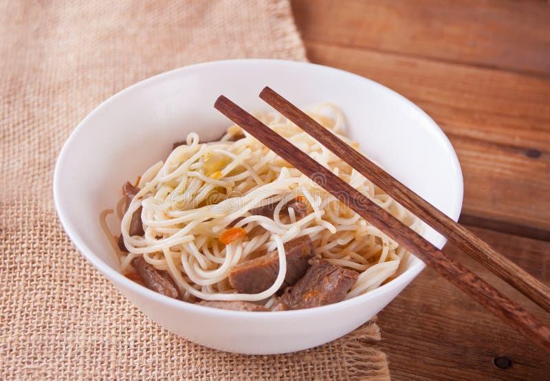 Азиатские лапши с говядиной, овощи в шаре с палочками, деревенской деревянной предпосылке Азиатский обедающий стиля Китайское япо стоковая фотография rf