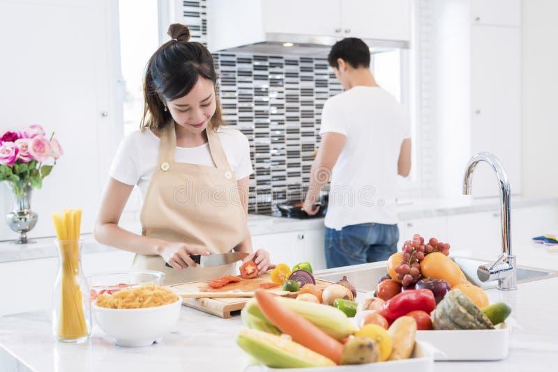 Азиатские любовники в кухне Овощи и варить куска женщины, человек делая спагетти, концепцию пар и семьи Медовый месяц и стоковая фотография rf