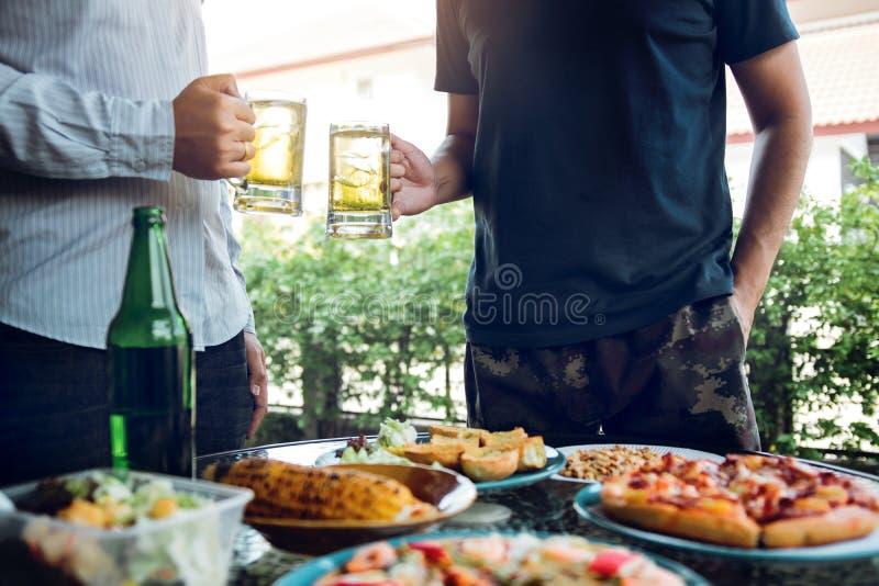 Азиатские люди общаются вне дома с сериями еды на таблице и держатся стекло пива внутри clinking и стоковые фото