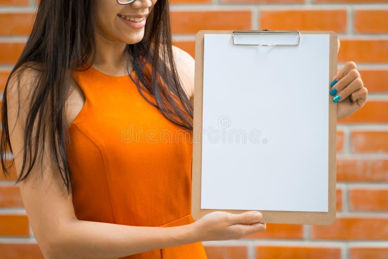 Азиатские молодые женщины держа доску сзажимом для бумаги и пустую белую бумагу стоковые фото