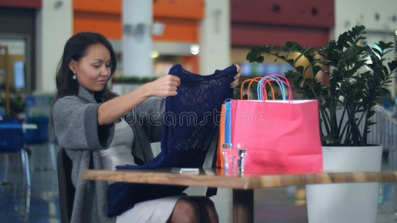 Азиатские молодые женщины при хозяйственные сумки смотря новое sittinf одежд в кафе стоковые фото