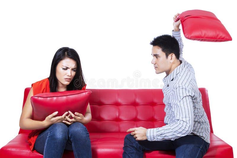 Азиатские молодые пары воюя с подушками стоковое фото