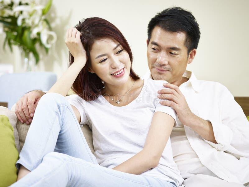 Азиатские пары беседуя дома стоковая фотография