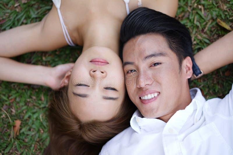 Азиатские пары лежа на траве стоковые изображения