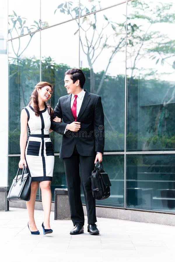 Азиатские пары дела идя работать стоковые фотографии rf