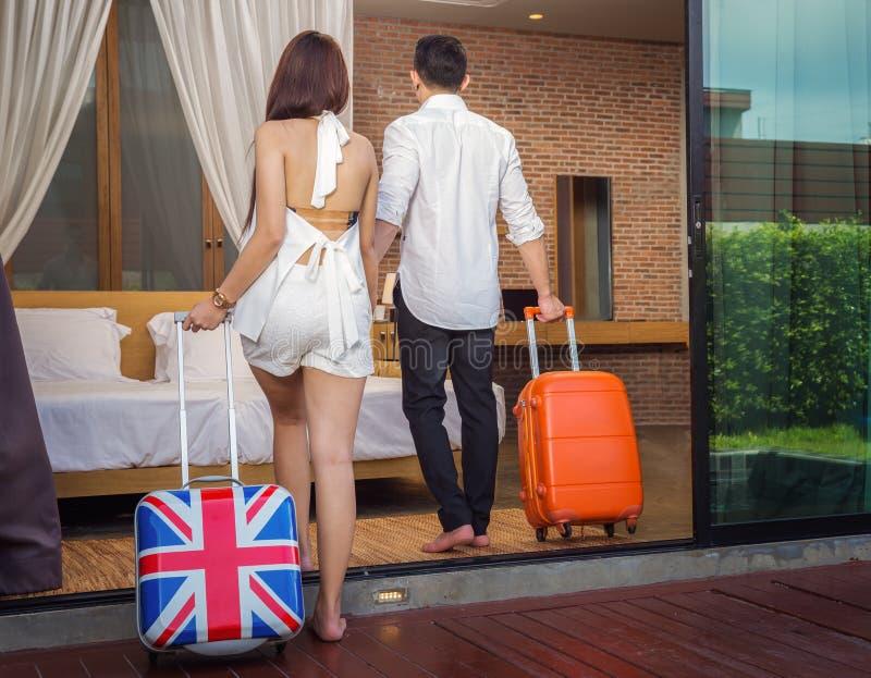 Азиатские пары идут для того чтобы положить комнату в постель в курорте стоковое фото rf