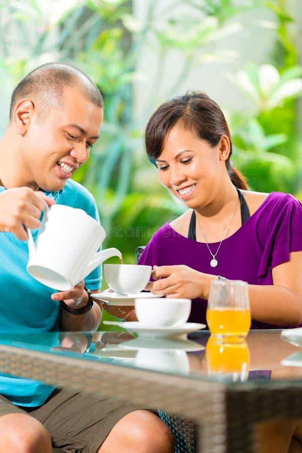Азиатские пары имея кофе на домашнем крылечке стоковые фотографии rf