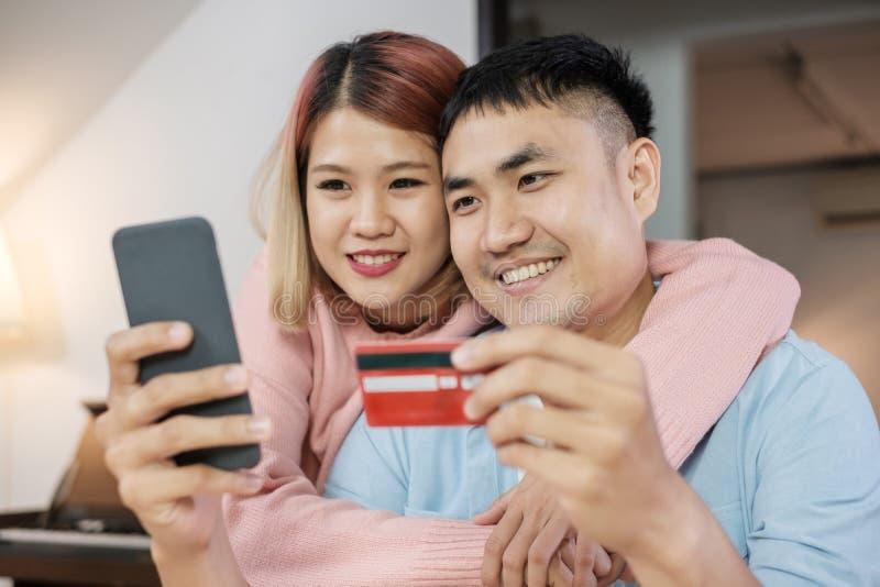 Азиатские пары используют мобильные покупки онлайн с кредитной карточкой совместно в живущей комнате дома пары в домашней концепц стоковая фотография rf