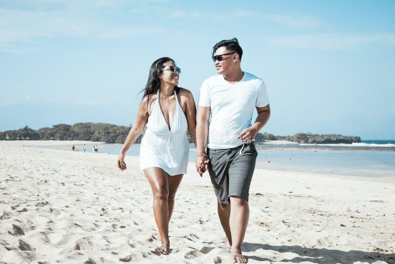 Азиатские пары идя на пляж тропического острова Бали, Индонезии стоковые фото