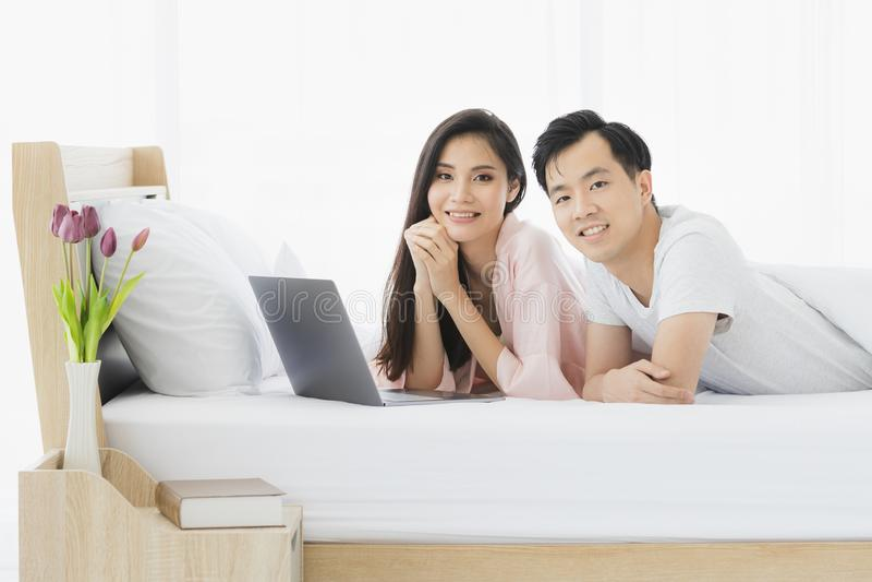 Азиатские пары лежат прональный на кровати в спальне стоковое фото