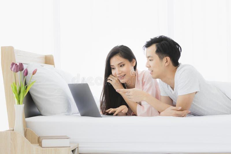 Азиатские пары лежат прональный на кровати в спальне стоковые изображения rf
