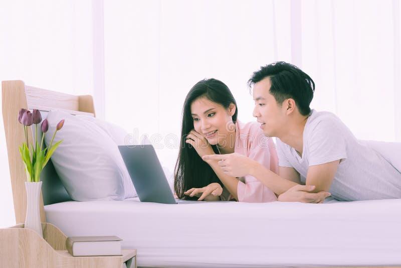 Азиатские пары лежат прональный на кровати в спальне стоковые фотографии rf