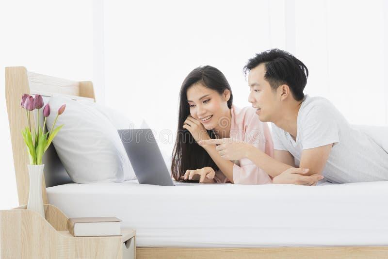 Азиатские пары лежат прональный на кровати в спальне стоковое фото rf
