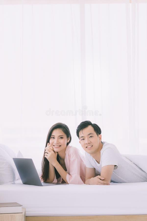 Азиатские пары лежат прональный на кровати в спальне стоковые изображения