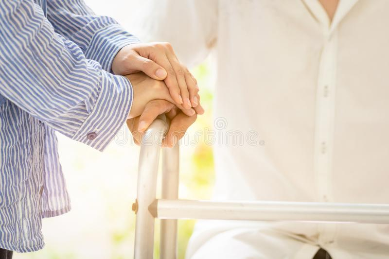 Азиатские пары семьи с ходоком во время реабилитации в доме, попечителе молодой женщины или руке удерживания руки жены супруга к стоковые фото