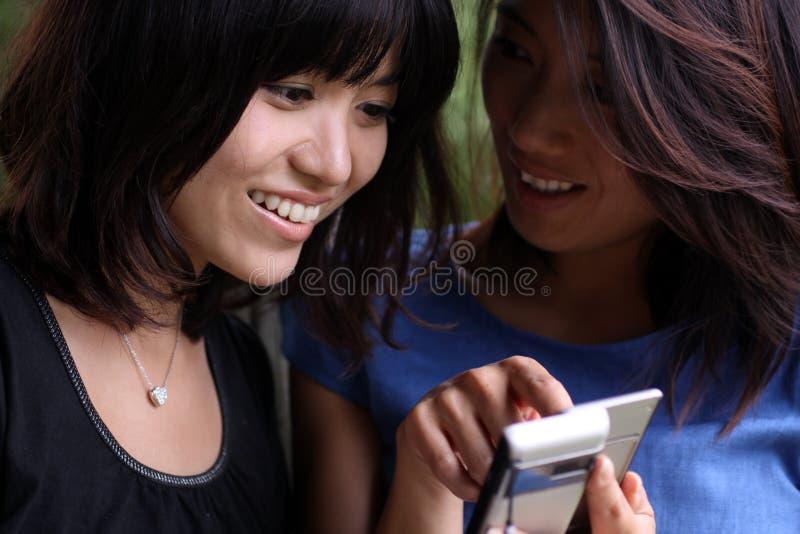 азиатские подруги мобильного телефона смотря 2 стоковые фото
