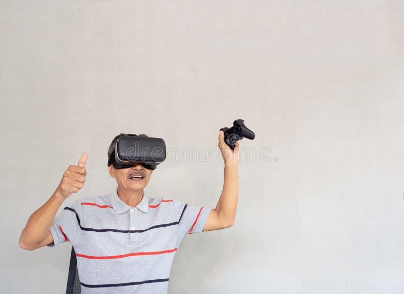 Азиатские пожилые люди наслаждаются современной технологией Онлайн-игры игры через стекла виртуальной реальности Образ жизни совр стоковые фотографии rf