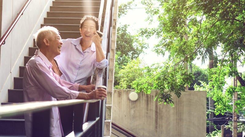 Азиатские пожилые профессиональные пары говоря внешнее утро в cit стоковая фотография