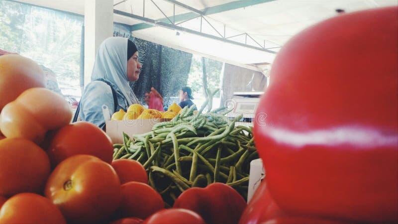 Азиатские покупки женщины на рынке овощей стоковые фотографии rf