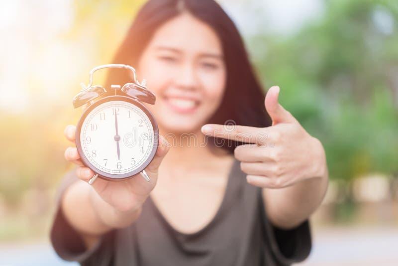 Азиатские рука женщин и палец пункта к ретро временам часов на часах ` 6 o, стоковые фотографии rf