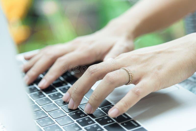 Азиатские руки женщины и пожененное кольцо имеют касаться и печатать на Ла стоковая фотография
