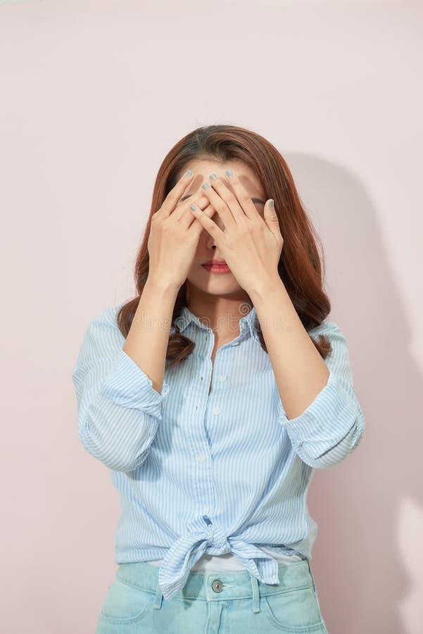 Азиатские руки женщины покрывая ее глаза от яркого солнечного света стоковое изображение