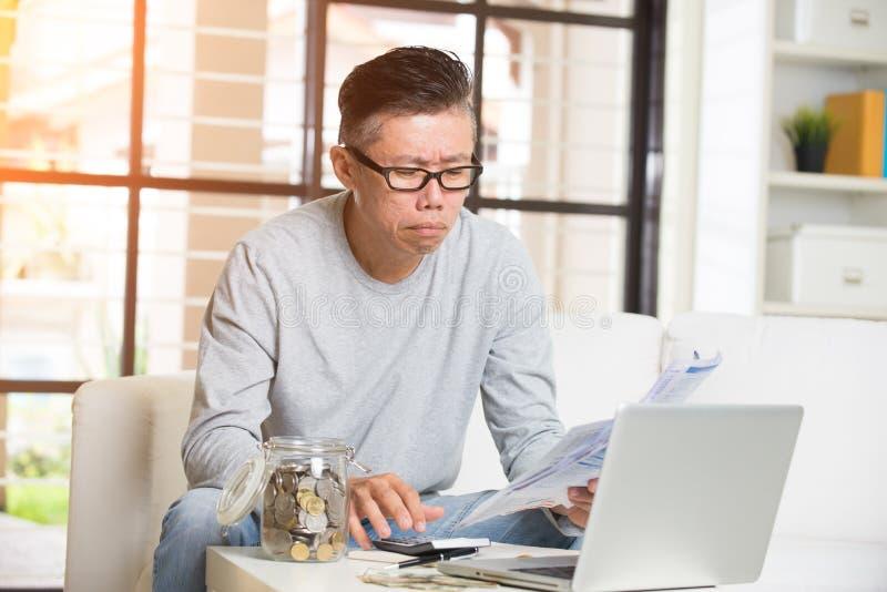 Азиатские созретые мужские оплачивая счеты стоковые фотографии rf