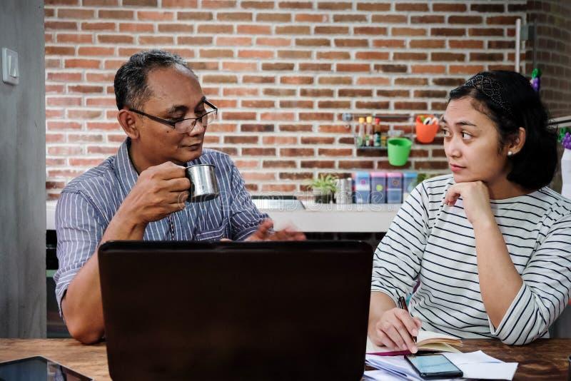 Азиатские сотрудники имея серьезное обсуждение дела в офисе кухни дома стоковое фото rf
