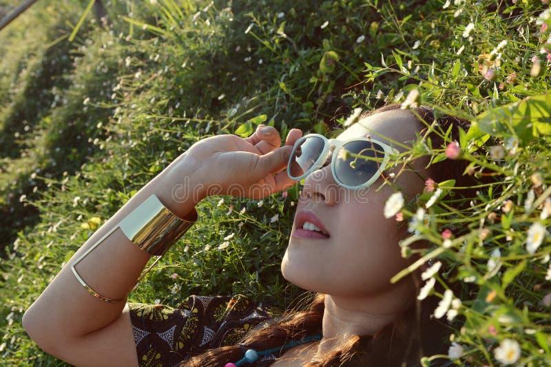 Азиатские солнечные очки носки женщины лежа в цветочном саде стоковая фотография rf