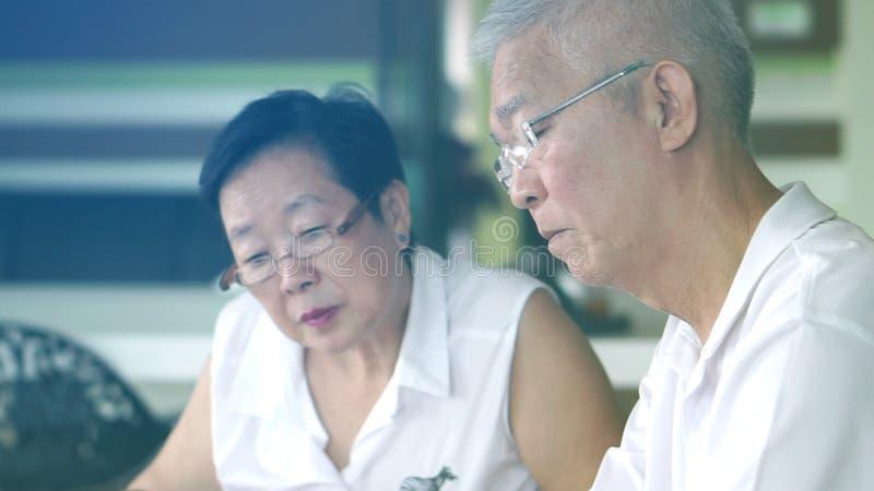 Азиатские старшие книги и журналы чтения пар совместно в библиотеке Концепция учить и исследования стоковое изображение rf
