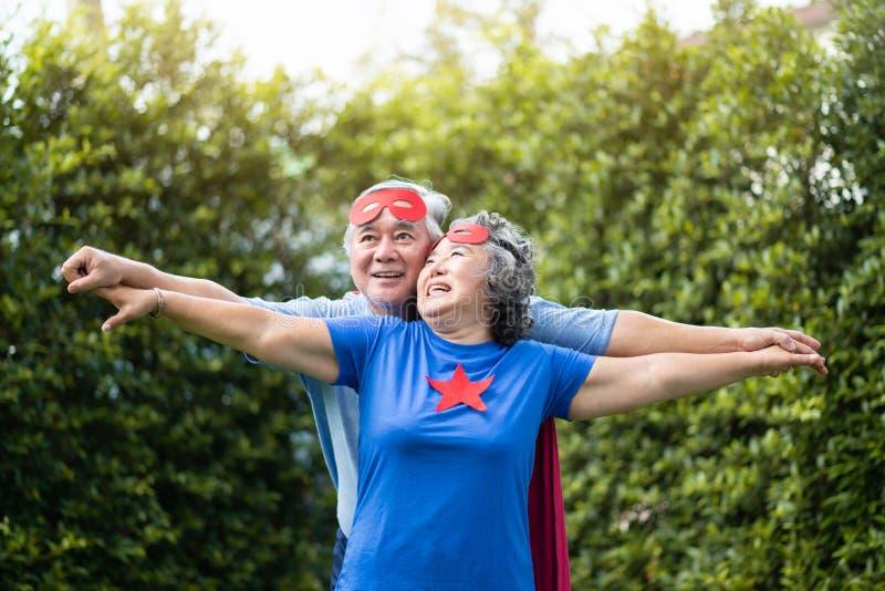 Азиатские старшие пары в костюме супергероя ослабляя стоковое изображение