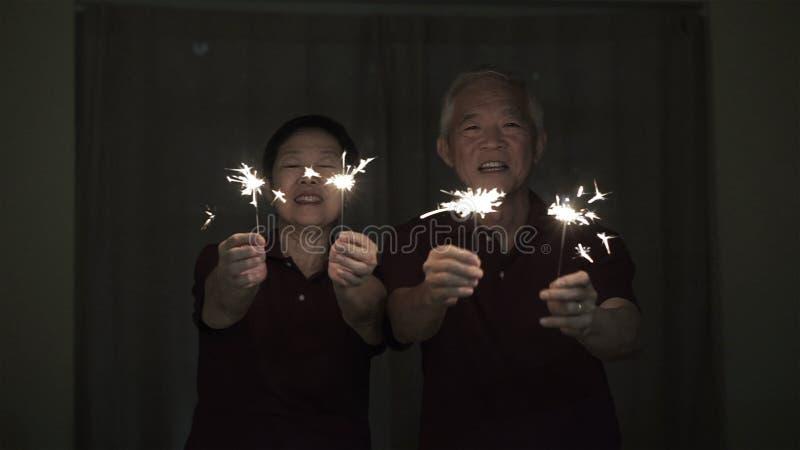 Азиатские старшие пары играя бенгальские огни, шутиху огня вечером Концепция празднуя жизнь стоковая фотография rf